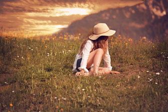 Mädchen mit Sonnenhut in der Wiese sitzend