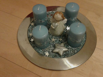 Adventkranz mit blauen Kerzen und einem Engel in der Mitte