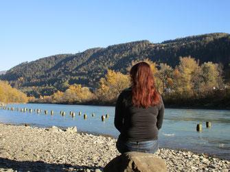 Mag. Julia Gheri von hinten vor einem Fluss und herbstlich verfärbten Bäumen