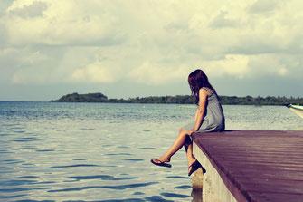 Mädchen am Steg sitzend lässt die Beine ins Meer baumeln