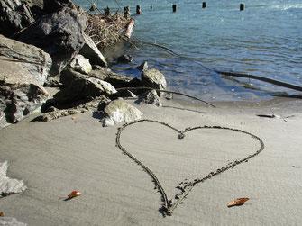 Herz im Sand am Wasser