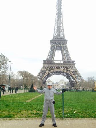写真は エッフェル塔の前でパリジャン風の竹垣悟