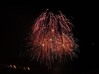 Auf dem Bild zu sehen: rotes Feuerwerk auf schwarzem Grund