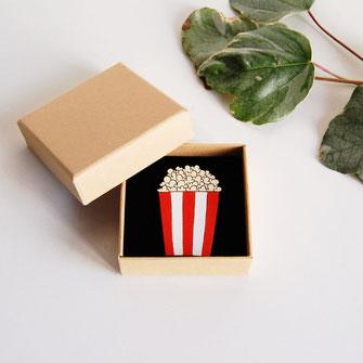 bijoux en bois, broche, pin's tendance à porter pour apporter de l'originalité à une tenue classique, réalisé en France à la main. ce bijoux avec système d'attache sécurisé est en forme de pot de pop corn rouge et blanc très gourmand, cinéma, soirée télé