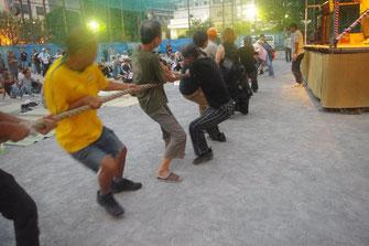 仕事で鍛えた力を発揮する綱引き競争の参加者