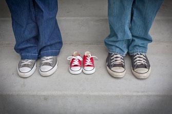 2 Erwachsene in Converse und ein leeres Paar Converse für Kinder