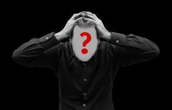 Mann mit Fragezeichen im Gesicht rauft sich die Haare