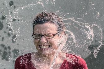 Frau wird mit Wasser bespritzt