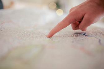 Finger sucht auf Landkarte Weg