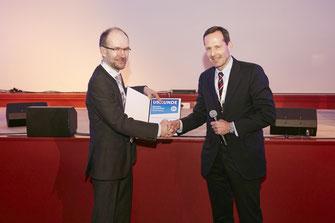 Prof. Dr. med. Alexander Enk (l.) übergibt Prof. Dr. med. Jörg Prinz die Urkunde zum Forschungspreis.  (Foto: Novartis)