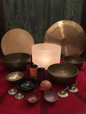 A collection of sound healing instuments, singing bowls, tingshals, drum, gong, rattles