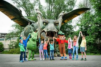 Kinder und Maskottchen der Drachenhöhle bei Furth im Wald stehen vor dem Further Drachen