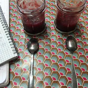 Sur une table de cuisine, deux pots de confiture de fraise avec deux cuillères et un cahier de remarques.
