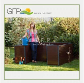 Blonde Frau gießt Pflanzen im lackierten Hochbeet - © GFP