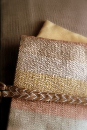 パステル色の伊兵衛織の帯。光沢のある八丈織のきものに合わせて春らしいコーディネートで。