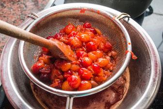 Wildpflaumen werden gekocht durch ein Sieb passiert