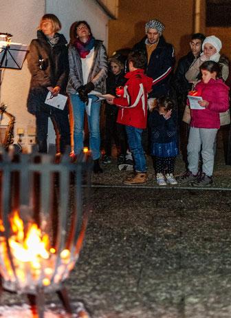 """Eine kleine Vorhut fühlt sich vom """"Adventsfenster"""" bereits angelockt. Wenig später bildeten mehr als 60 Besucher einen großen Kreis um das offene Feuer. Eingeladen dazu hatte die Initiative Gemeinsam für Flüchtlinge in RSKN (Foto: Uwe Mönninghoff)"""