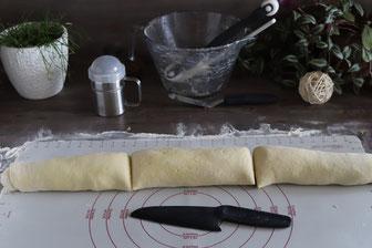 Teig mit dem Nylonmesser auf der Teigunterlage teilen