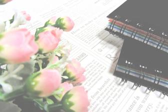 ピンクのバラの花束と広げられた資料、リングファイル。