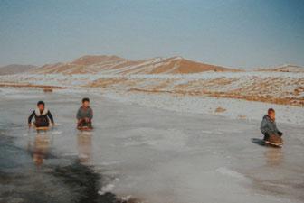 凍ったセルベ川を座りすべりで遊ぶ子どもたち(1985年11月、ウランバートル)