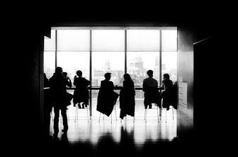 Menschen diskutieren im Schatten