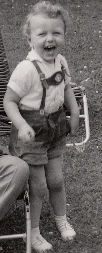 Die allerjüngste Episode in der Bach-Genealogie: ein kleiner Junge lacht fröhlich zur KAmera. Er hat kurze Lederhosen an, es ist ein schwarz-weißen Bild. Es ist im Garten aufgenommen, auf dem Rasen vor einer Liege. Der Junge lacht, es ist Peter Bach jr.!