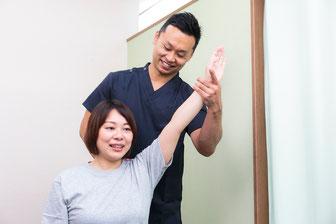 患者の筋肉・関節・神経を検査している鍼灸師