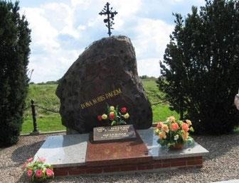 """Denkmal mit der Aufschrift """"Beschenkt uns mit Frieden"""", umflochten mit 120 Efeublättern, ein Blatt für jedes Opfer."""