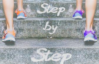 Zwei Personen laufen Schritt für Schritt die Stufen hoch