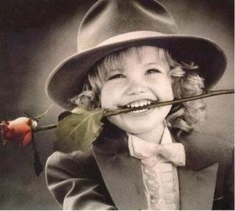 Niño con traje y flor en la boca regalando una sonrisa