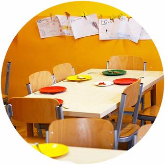 Kita-Reinigung, gedeckter Tisch und Kinderbilder an der Wand