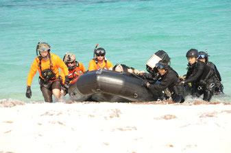 海上で遭難した米兵に見立てた人形をボートを使って救助する航空自衛隊救難隊員と米空軍の隊員ら=7日午前、うるま市の浮原島