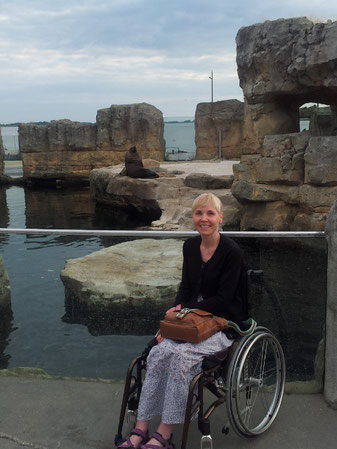 Melli at the Zoo at the Sea in Bremerhaven, standing with her wheelchair in front of the sea lions.