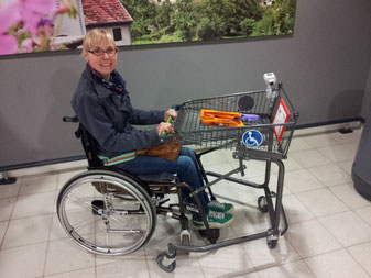 Melli with an wheelchair adapted shopping cart in a supermarket nearby.