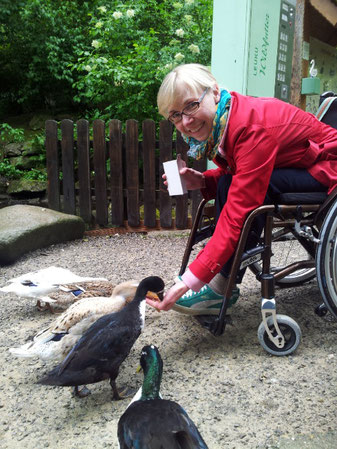 Melli sitzt im roten Mantel vornübergebeugt im Rollstuhl und fütttert ein paar Enten, die ihr aus der Hand fressen.