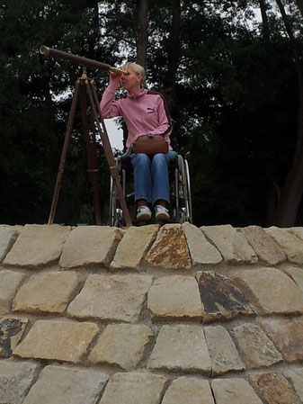 Melli in her wheelchair on top of a pyramid of stone, looking through an antique telescope, in search of an independent life.