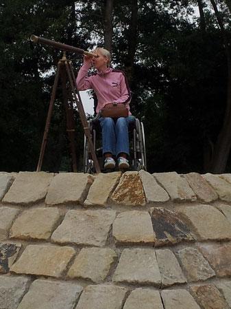 Melli steht mit ihrem Rollstuhl auf einer Steinpyramide und blickt mit einem antiken Teleskop in die Ferne, auf der Suche nach einem selbstbestimmten Leben.