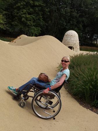 Melli steht mit ihrem Rollstuhl schräg hangaufwärts auf einer künstlichen Sanddüne.