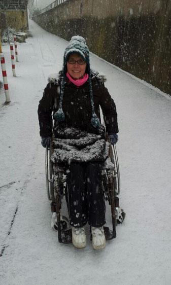 Melli und ihr Rollstuhl stark eingeschneit auf einem verschneiten Weg