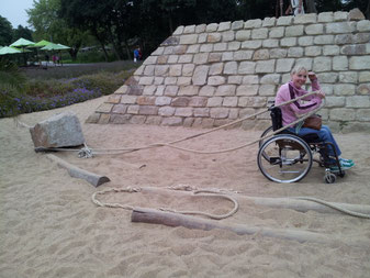 Melli in her wheelchair standing in deep sand, trying to pull a squared stone with a thick rope.