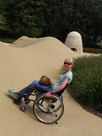 Melli in her wheelchair, trying to climb an artificial sand dune.