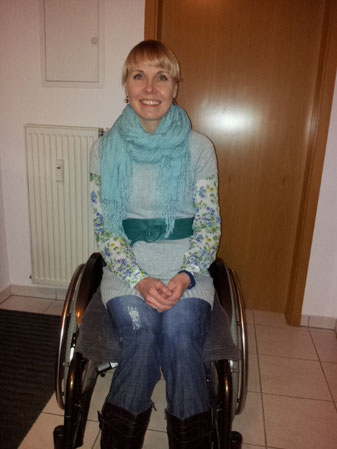 Melli in her wheelchair smiling at all the people, that support mach-melli-mobil with their donations.