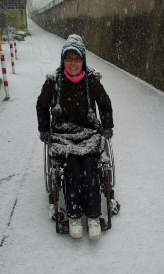 Melli in her wheelchair standing in deep snow while she is covered with snow herself.