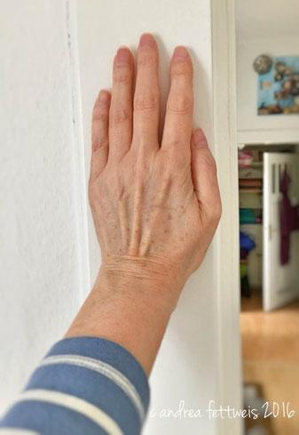 Dehnen des Schultergelenks vor dem Körper funktioniert leichter, wenn man die Hand zwischendurch gegen die Wand presst.