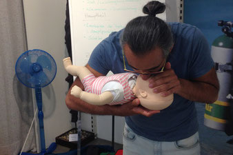 Mann hilft einem verletzten Kind beim Care for Children Kurs, 1. Hilfe bei Kindern