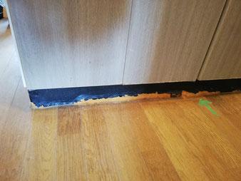 キッチン下部の板が腐食してふやけている様子