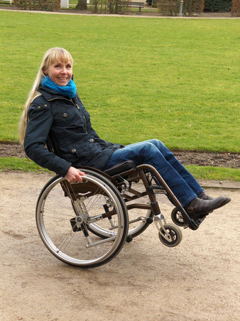 Melli is doing a wheelie with her wheelchair in the park.