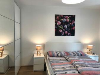 Ferienwohnung Schlafzimmer; weißgeöltes Echtholzparkett und ein sorgfältig ausgewähltes Lichtdesign schaffen entspannte Atmosphäre.
