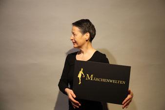 Seitliches Portrait von Frau stehend mit Poster in der Hand