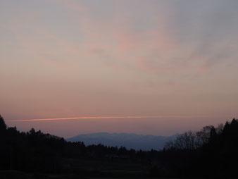 夕焼けに映える焼石連峰と飛行機雲